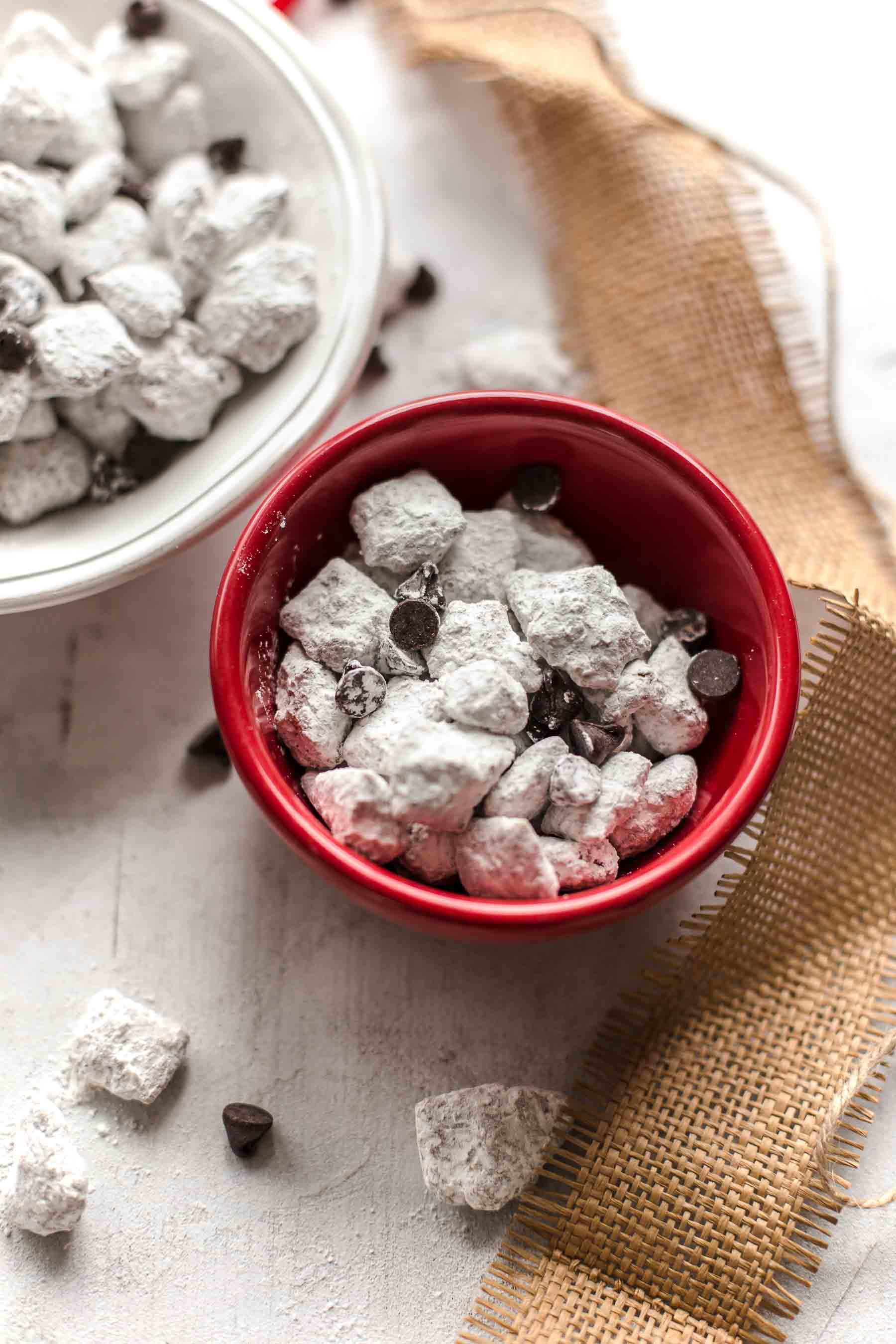 small red bowl of puppy chow next to a larger white bowl
