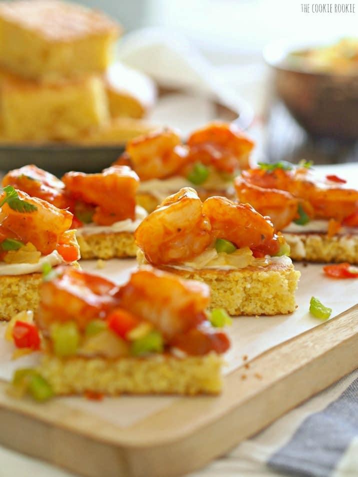 creole shrimp and cornbread bruschetta on wooden tray