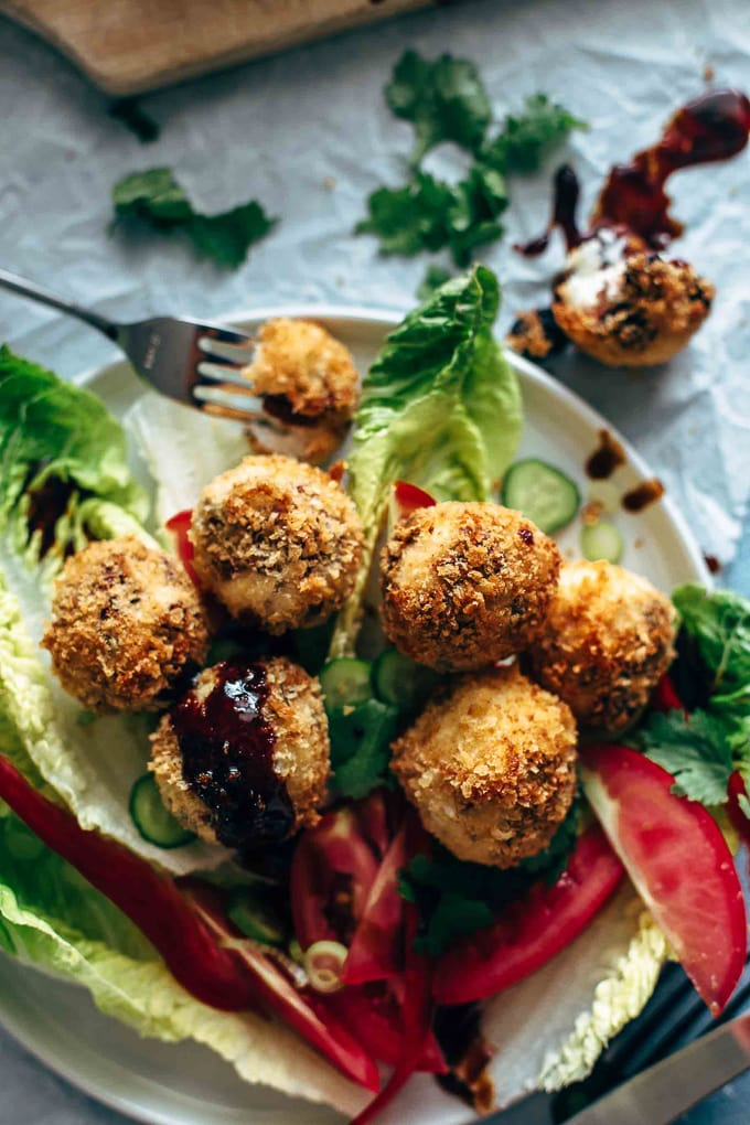A plate of greens topped with fried goat cheese balls