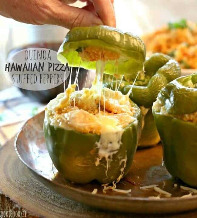 Quinoa Hawaiian Pizza Stuffed Peppers with hand
