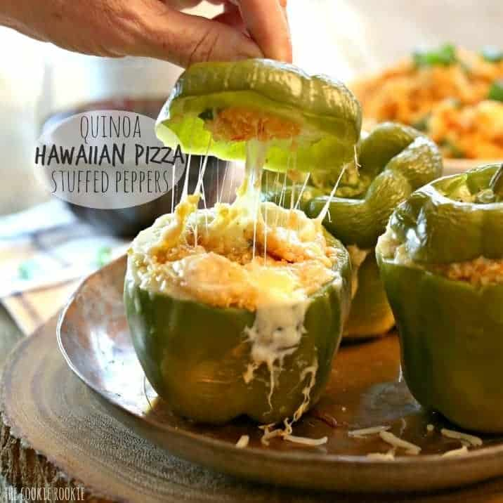 Quinoa Hawaiian Pizza Stuffed Peppers with a hand pulling top of pepper off