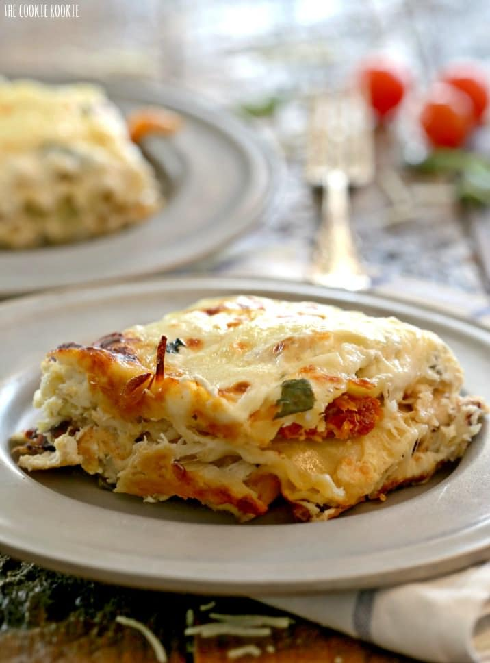 Creamy White Chicken Caprese Lasagna stuffed with mozzarella, cream cheese, artichokes, sundried tomatoes, and basil. SO delicious! The perfect comfort food! | The Cookie Rookie