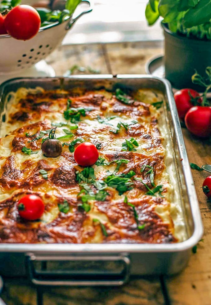lasagna on a table with fresh tomatoes
