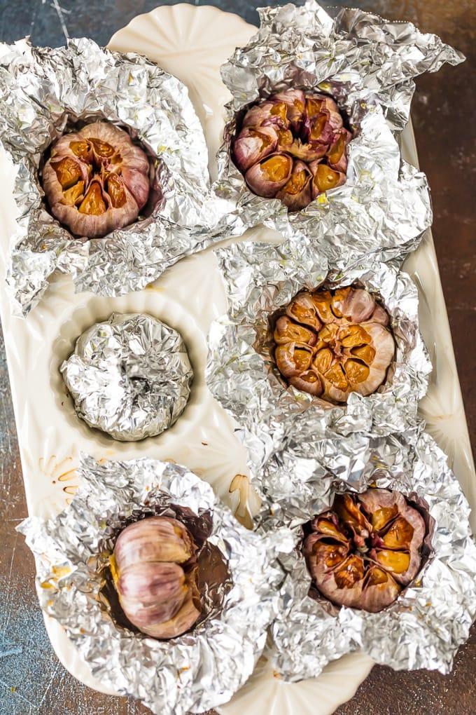 garlic covered in foil in cupcake baking dish