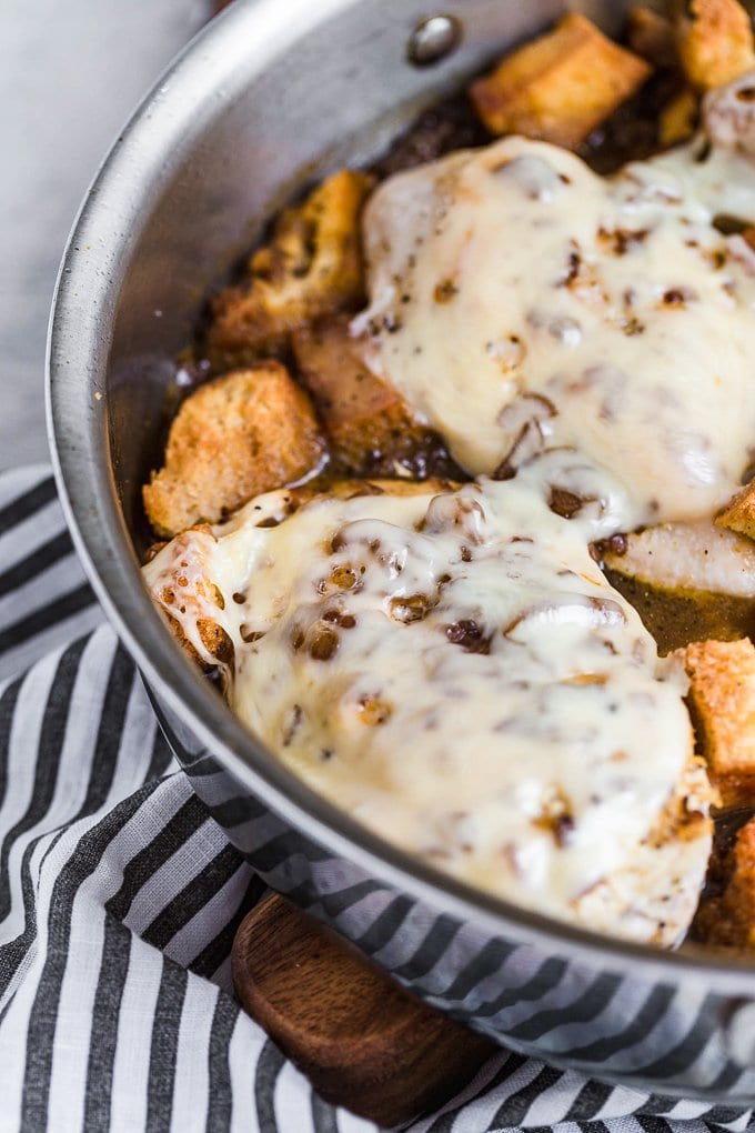 Chicken breast covered in cheese, with croutons in a skillet