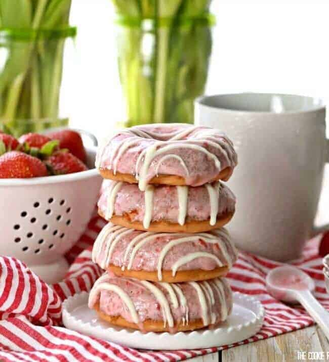 Strawberries and Cream Cake Mix Donuts on a plate in front of a coffee mug and colander of strawberries