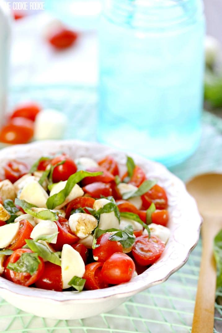 A plate of food on a table, with Salad and Caprese salad