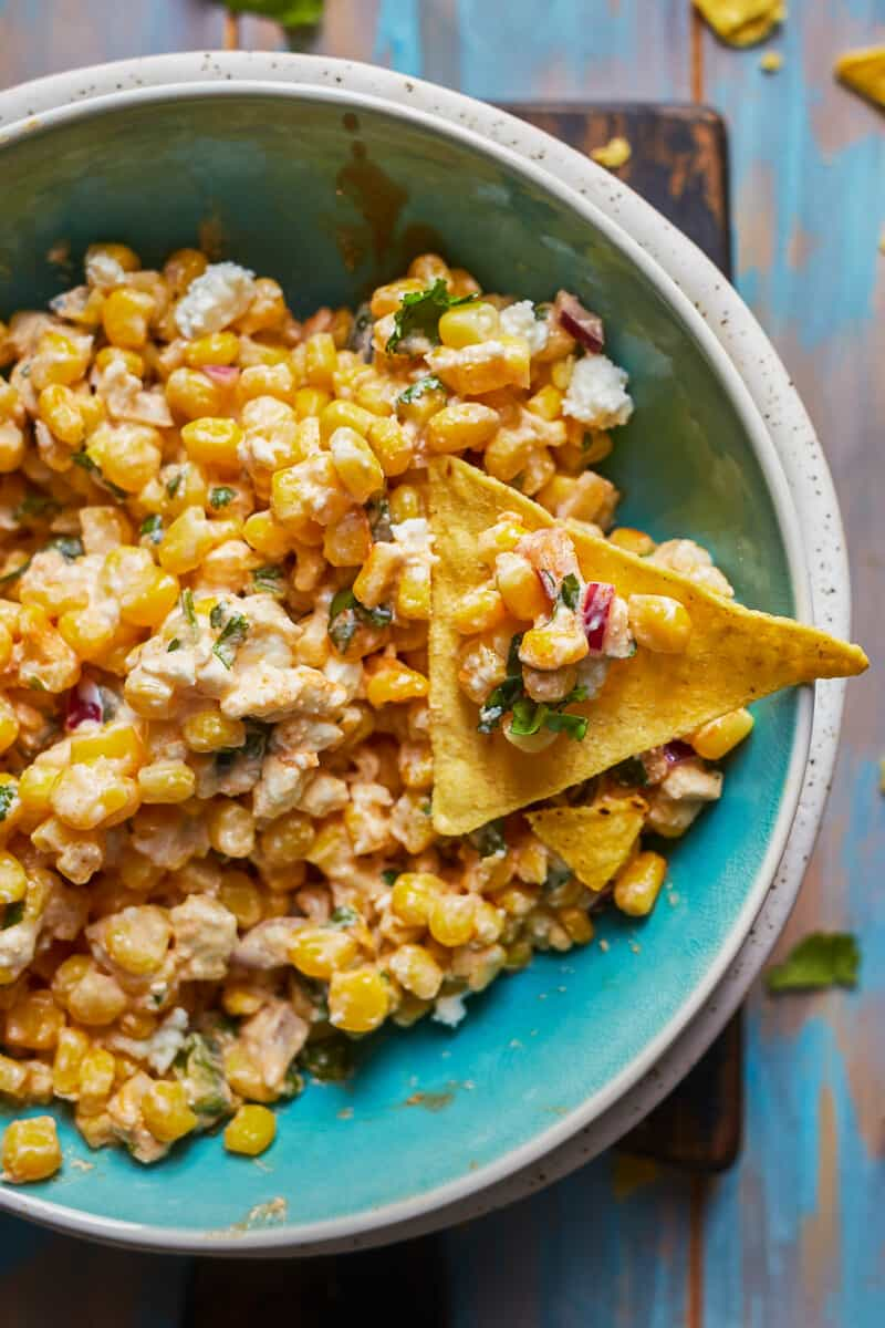dipping chip into bowl of healthy mexican street corn dip