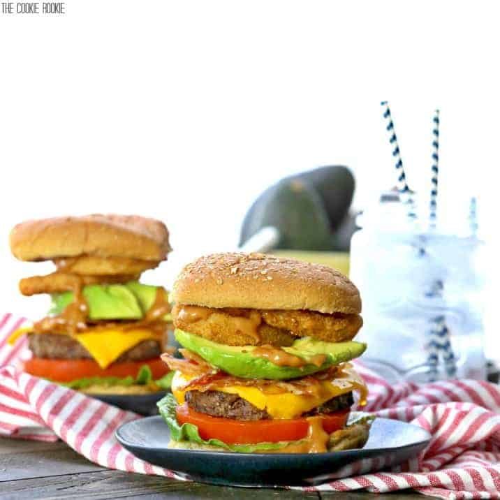 two burgers loaded with onion rings, avocado, and more