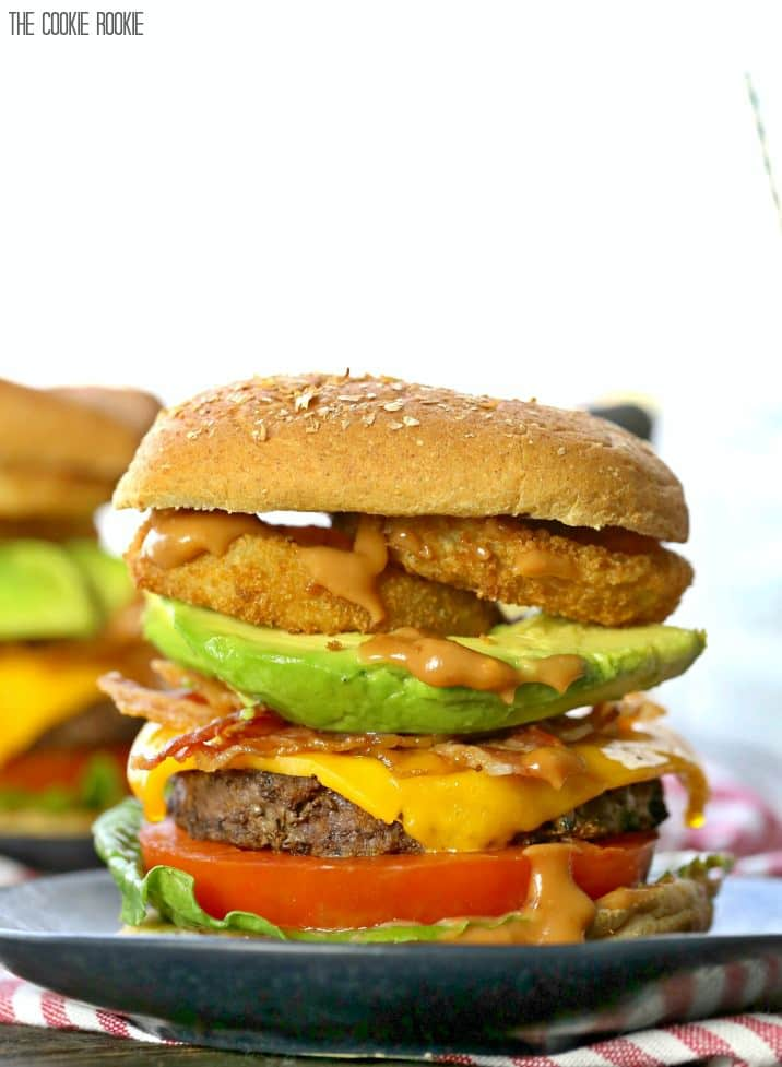 cheeseburger topped with bacon, avocado, onion rings, and spicy mayo