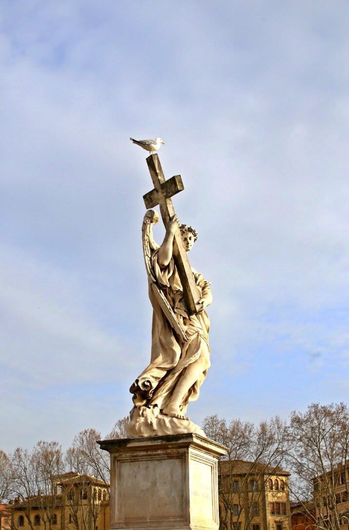 statue of person holding cross