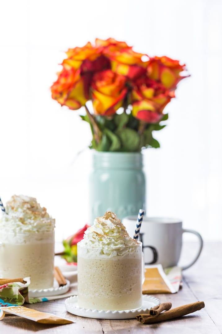 chai tea milkshakes in front of a vase of roses