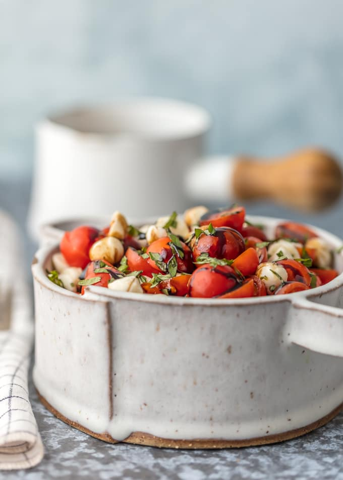 caprese salad topped with fresh basil in a bowl
