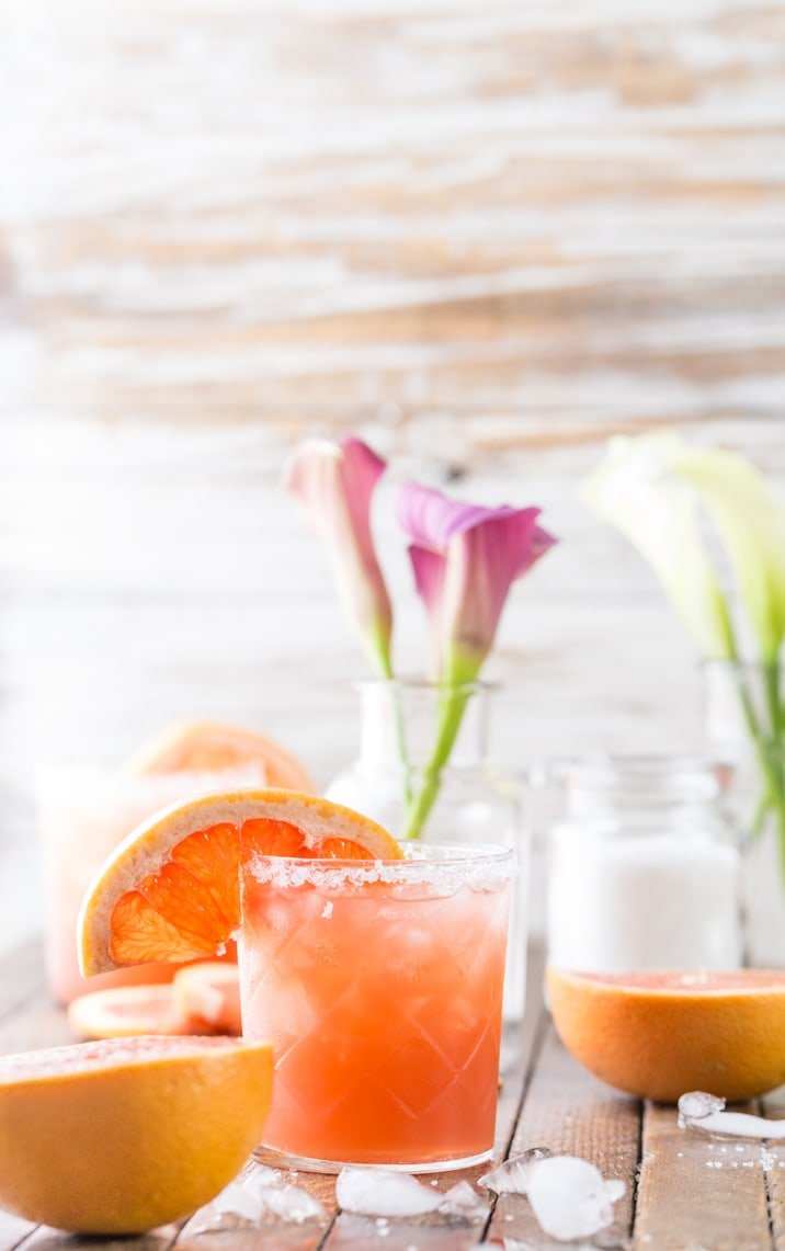 cocktail on table with grapefruits and flowers