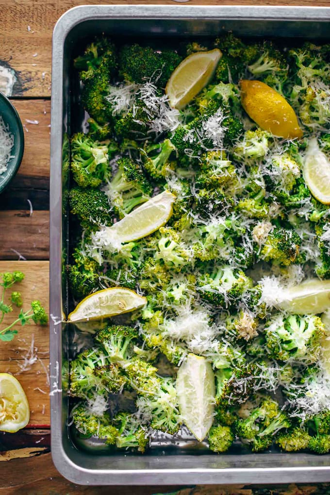 broccoli on a baking sheet with parmesan and lemon wedges