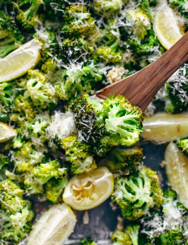 broccoli on a baking dish with lemon wedges and parmesan