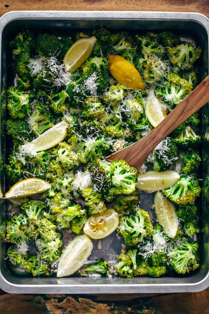 baking sheet of lemon parmesan roasted broccoli and wooden spoon