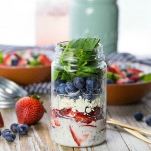 mason jar salad on a table surrounded by berries
