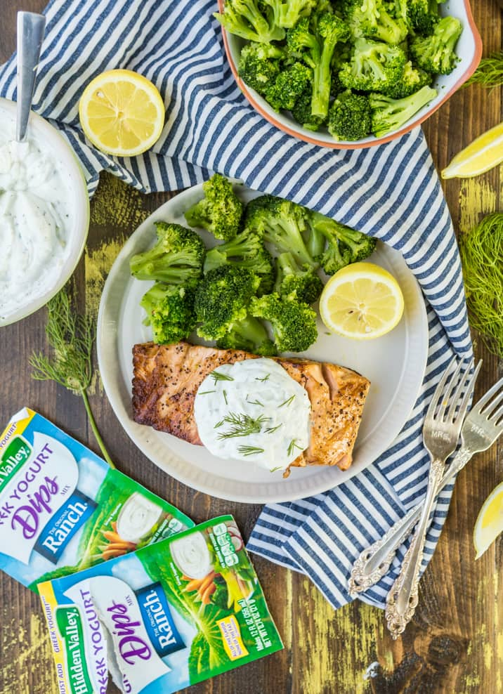 tablescape with a plate of salmon and broccoli, a bowl of broccoli, a striped dish towel, and packets of greek yogurt ranch