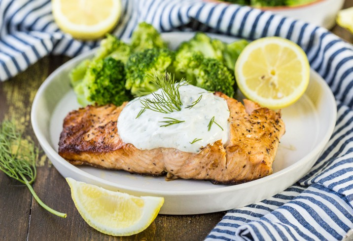 a plate of salmon and broccoli on a table with a striped dish towel and sliced lemons