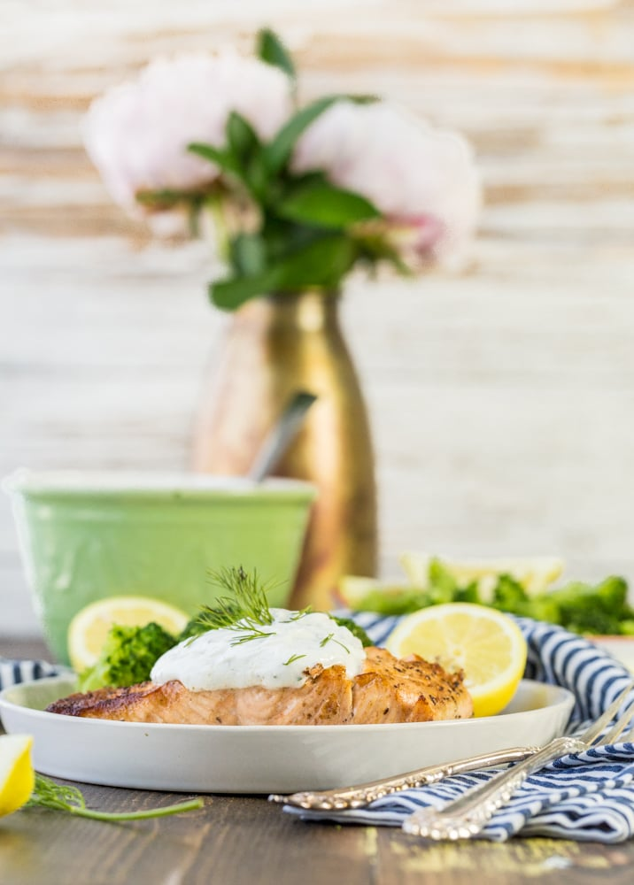 a plate of salmon on a table with a dish towel and a green bowl in the background