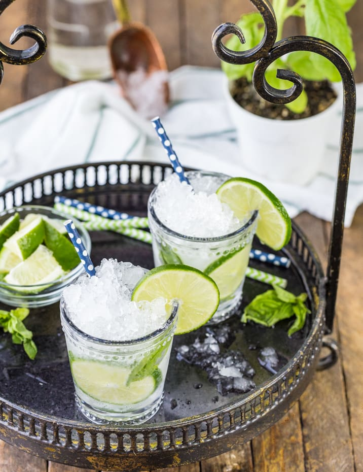 mojitos on a tray with sliced lime wedges in a bowl
