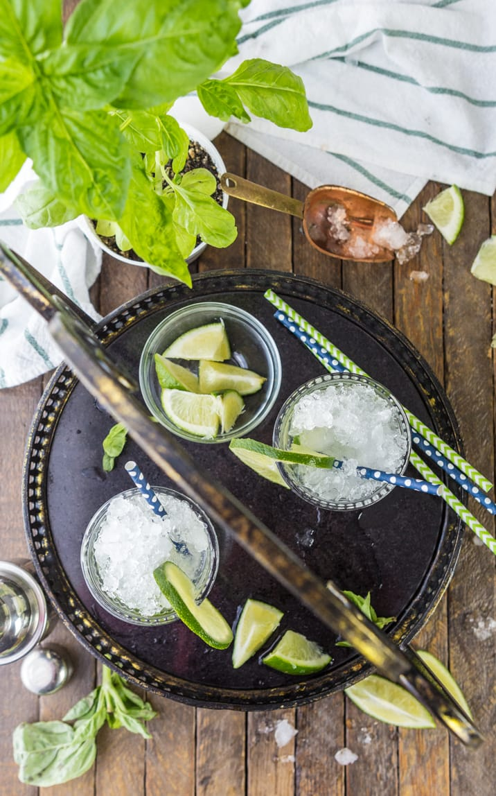 top view of mojitos with straws, lime wedges, and crushed ice