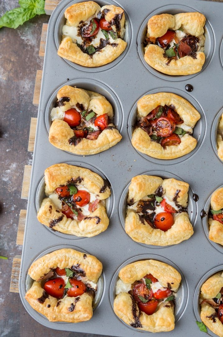 Puff Pastry Caprese Cups! We love these hot AND cold. Tomato, Mozzarella, Prosciutto, Basil, and Balsamic Reduction. PERFECTION!
