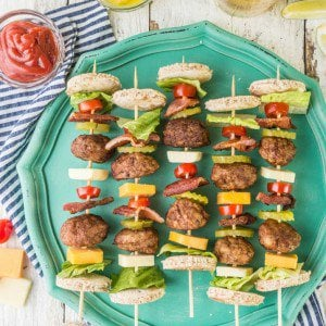 deconstructed bacon cheeseburger kebabs on a teal plate