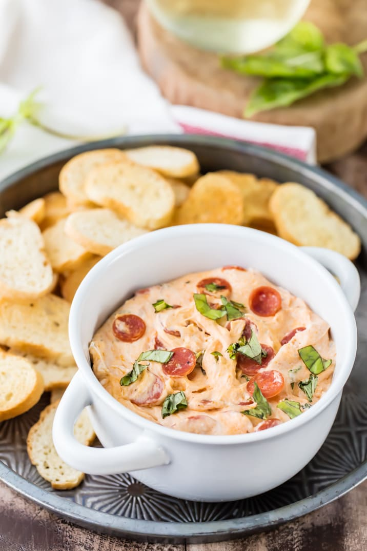 Slow Cooker Pepperoni Pizza Dip! This is the perfect cheesy dip for tailgating! Throw the ingredients in a slow cooker and forget about them! DELICIOUS!