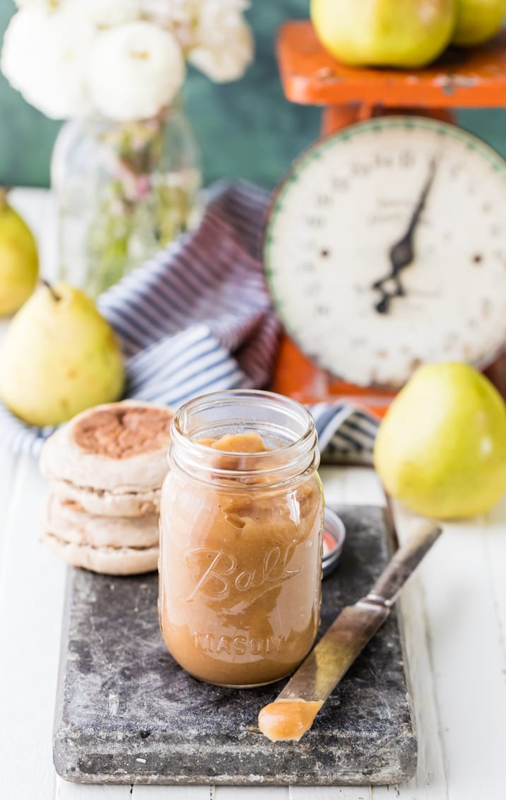 jar of pear butter and english muffins on a table with pears