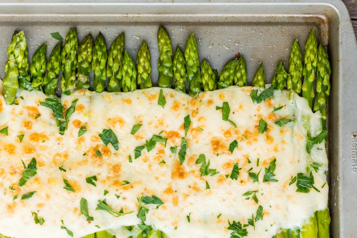 A baking tray lined with cheesy asparagus