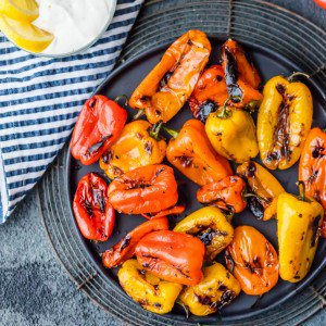 red, orange, and yellow blistered peppers on plate
