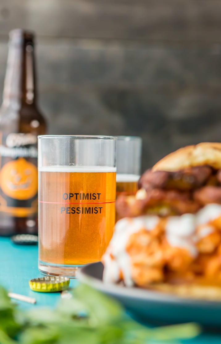 glass of beer in focus, buffalo chicken sandwich blurred in the foreground