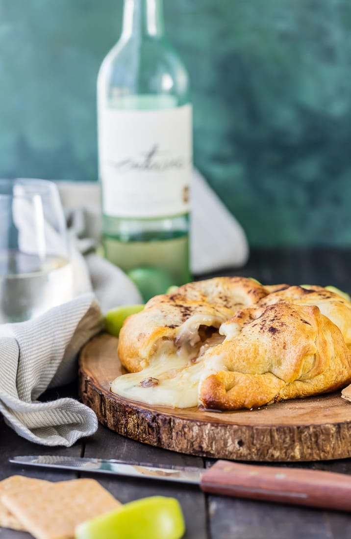 apple pie baked brie on wooden board with knife and wine bottle
