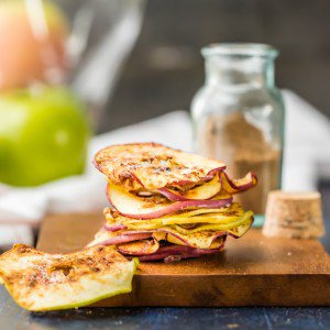 cinnamon sugar apple chips stacked up on a wooden cutting block