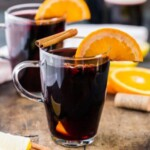 glasses of mulled wine topped with oranges and cinnamon sticks