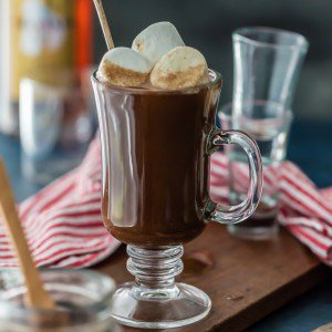 chocolate hot buttered rum in a glass mug topped with big marshmallows sitting on a table
