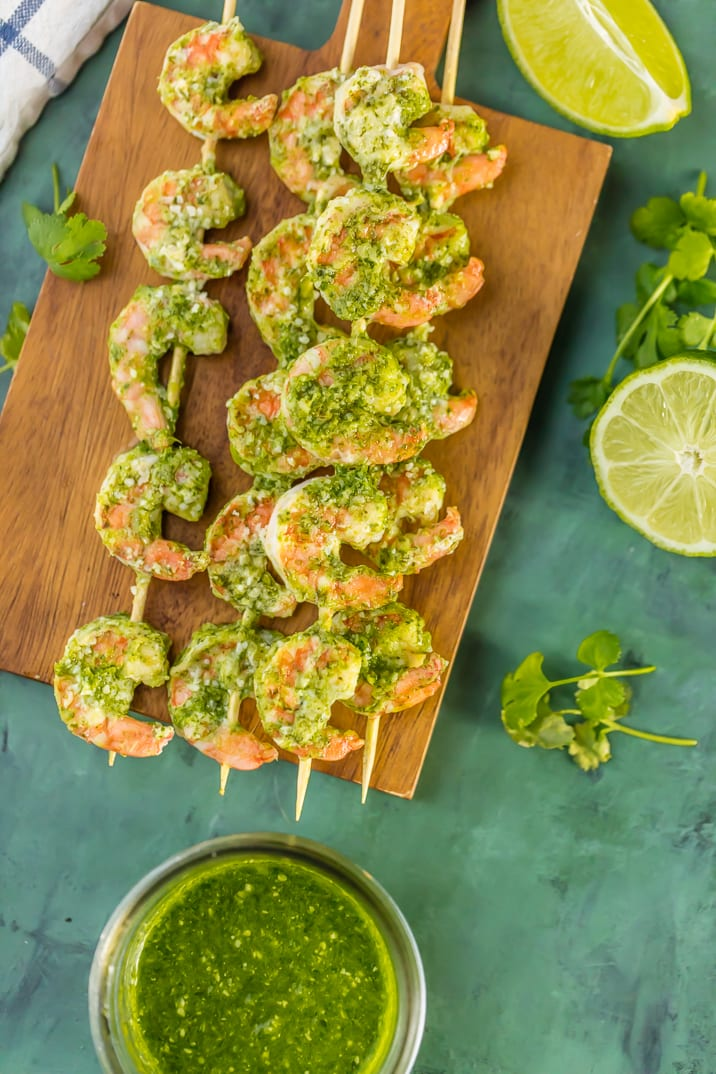 Closer shot of pesto shrimp on cutting board with lime wedges and pesto sauce