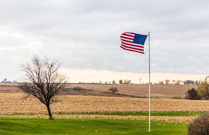 American flag waving on a pole next to a corn field