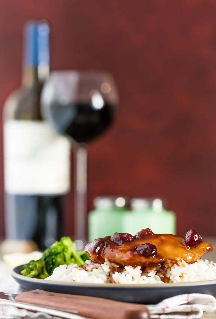 plate of slow cooker cranberry chicken with glass of wine in background