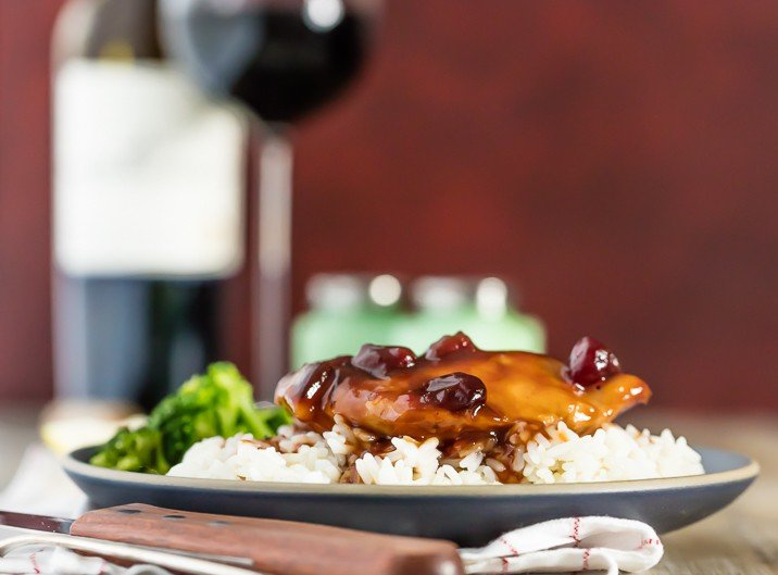 slow cooker cranberry chicken and rice with broccoli, glass of wine in background