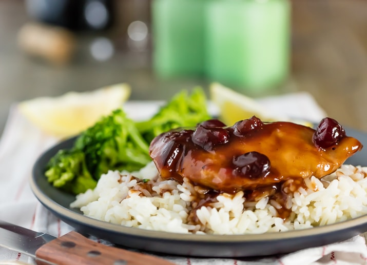 plate of slow cooker cranberry chicken on rice with broccoli