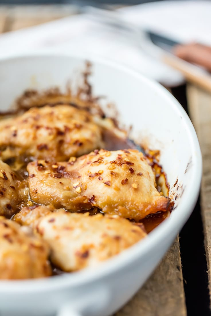 close up of baked honey garlic chicken in white baking dish