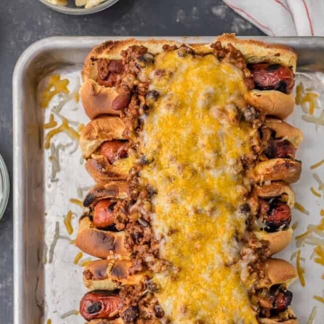 This Chili Dog Recipe all baked together on a sheet pan is the BEST Chili Dog Recipe ever! These Chili Cheese Dogs topped with the best hot dog chili recipe. If you're in the mood for comfort food; toasted buns, grilled hot dogs, best ever chili, and of course tons of cheese; this recipe is for you!