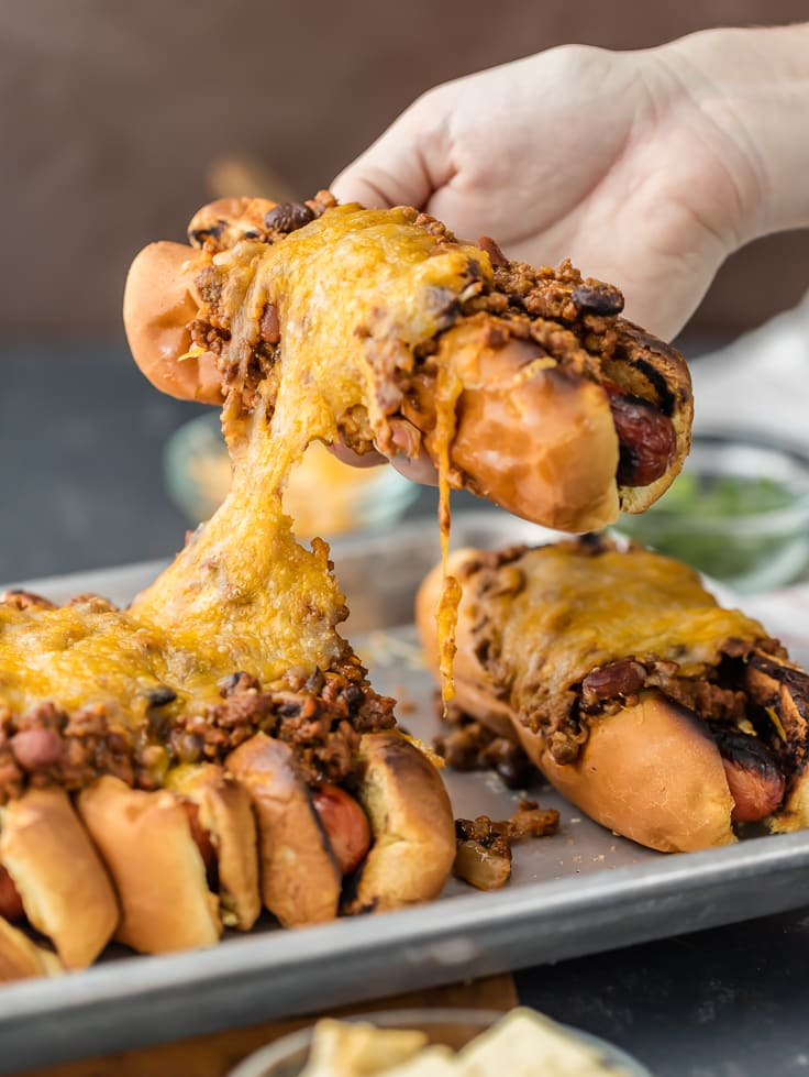 pulling a chili cheese dog off a tray of chili dogs