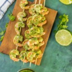 pesto shrimp skewers on a wooden cutting board
