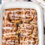 cinnamon roll french toast bake in a white baking dish drizzled with frosting