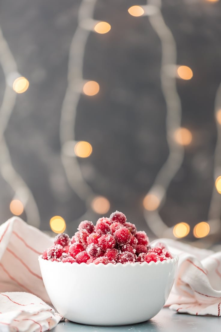 white bowl of easy sugared cranberries with white lights in background