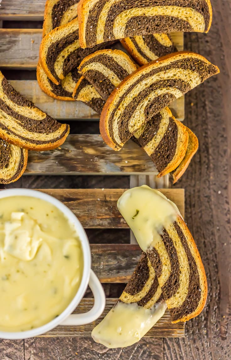 top view of marbled rye crostini slices and a bowl of fondue on wooden palate